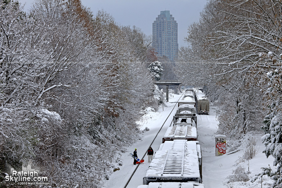 Snowy Norfolk Southern train passes snowboarders in Raleigh